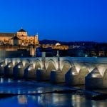 Cityscape of Cordoba at sunset with Roman bridge and Mezquita