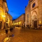 Cobbled street between old church and houses in Alba, Italy