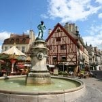 Famous fountain, characteristic houses and colorful carousel in Dijon, Burgundy