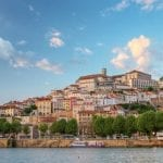 Old town of Coimbra glows at sunset under a pretty summer sky